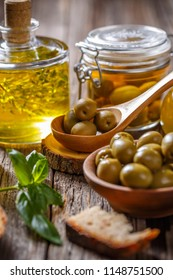 Green olives and olive oil on wooden background