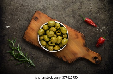 Green olives with peppers in ramekin on cutting board on dark ba