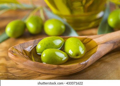 Green olives and virgin olive oil on a wooden spoon