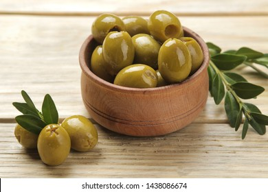 Green olives in a wooden bowl with leaves on a natural wooden table. close-up.
