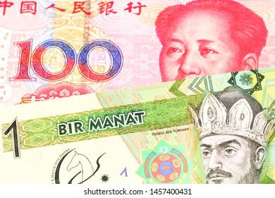 A green one manat note from Turkmenistan close up in macro with a red, one hundred yuan renminbi bank note from the People's Republic of China