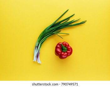 Green Onion and Red Bulgarian pepper on yellow background