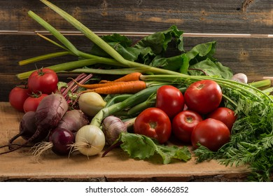 Green onions, garlic, carrots, beet and tomatoes against the background of old grey boards