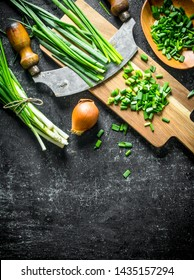 Green and onions with a large knife. On dark rustic background