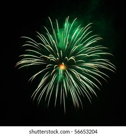 A green and orange burst of fireworks in the night sky