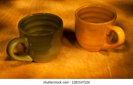 """A green and orange cup shot on a wood background. Used """"painting by light"""" for this exposure."""