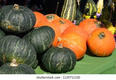 Green and orange pumpkins are sold at a farmer market