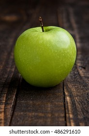 Green organic healthy apple on wooden board. Healthy food