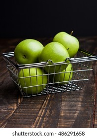 Green organic healthy apple in shopping basket on wooden board. Healthy food