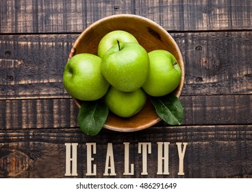 Green organic healthy apples in bowl on wooden board. With sign on the bottom