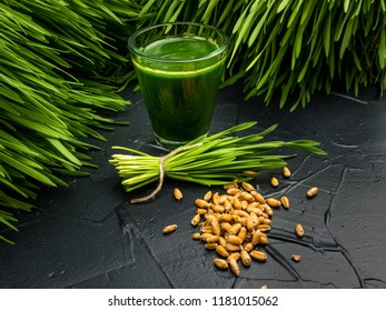 Green organic wheat grass drink over dark wood background,top view ,young grass stage.