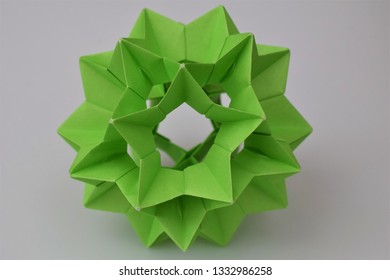 Green origami electra on white background
