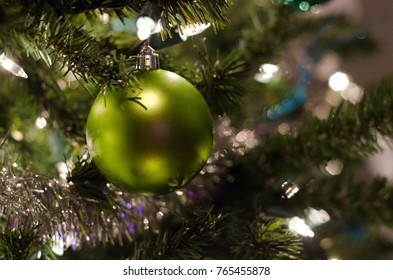 Green Ornament on Lit Christmas Tree