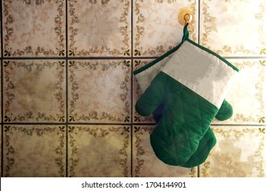 Green oven mitts hang on old-fashioned wall with pattern tiles antique design retro