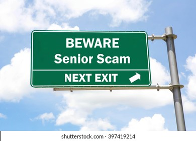 Green overhead road sign with a Beware of a Senior Scam Next Exit concept against a partly cloudy sky background.