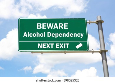Green overhead road sign with a Beware Alcohol Dependency Next Exit concept against a partly cloudy sky background.