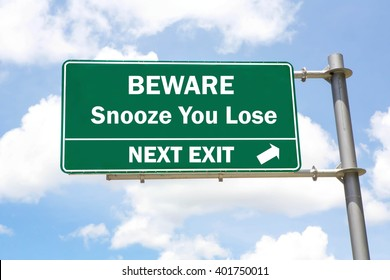 Green overhead road sign with a Beware of a Snooze You Lose Next Exit concept against a partly cloudy sky background.