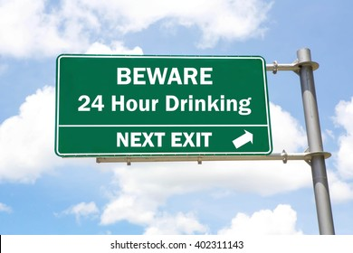 Green overhead road sign with a Beware of 24 Hour Drinking Next Exit concept against a partly cloudy sky background.