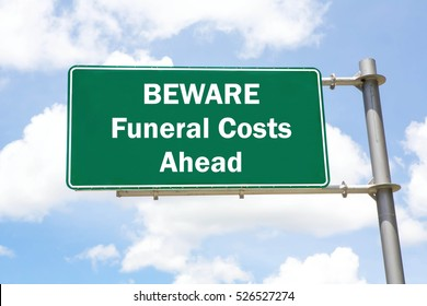 Green overhead road sign with a Beware Funeral Costs Ahead concept against a partly cloudy sky background.