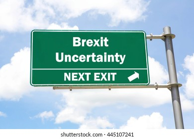 Green overhead road sign with a Brexit Uncertainty Ahead concept against a partly cloudy sky background.