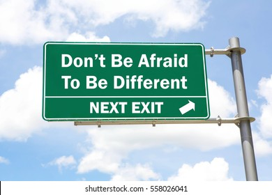 Green overhead road sign with a Don't Be Afraid To Be Different Next Exit concept against a partly cloudy sky background.