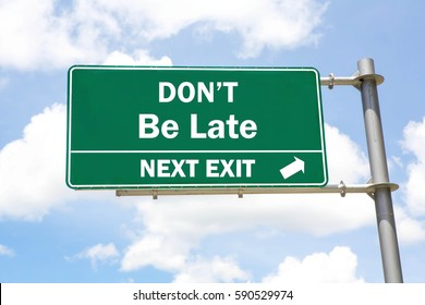 Green overhead road sign with a Don't Be Late Next Exit concept against a partly cloudy sky background.