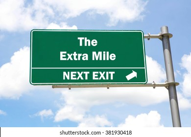 Green overhead road sign with a Go The Extra Mile Next Exit concept against a partly cloudy sky background.