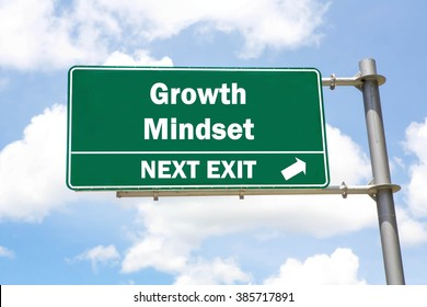 Green overhead road sign with a Growth Mindset Next Exit concept against a partly cloudy sky background.