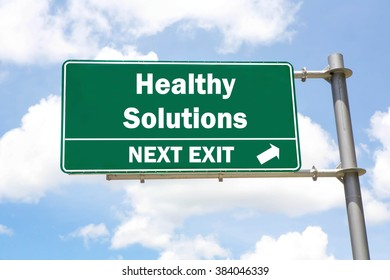 Green overhead road sign with a Healthy Solutions Next Exit concept against a partly cloudy sky background.