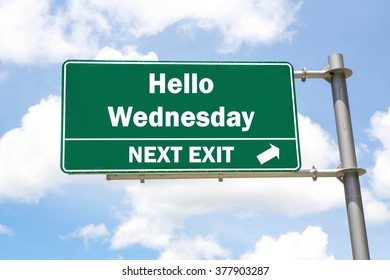 Green overhead road sign with a Hello Wednesday Next Exit concept against a partly cloudy sky background.