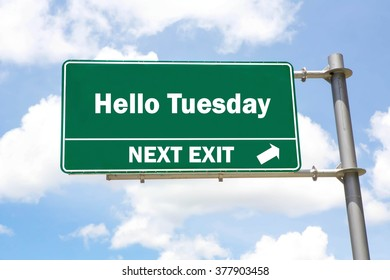 Green overhead road sign with a Hello Tuesday Next Exit concept against a partly cloudy sky background.