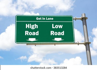 Green overhead road sign with the instruction to get in lane with a High Road or Low Road concept against a partly cloudy sky background.