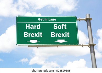 Green overhead road sign with the instruction to get in lane with a Hard Brexit or Soft Brexit concept against a partly cloudy sky background.
