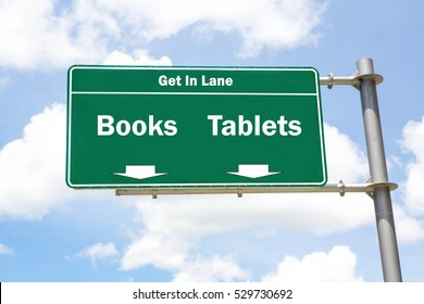 Green overhead road sign with the instruction to get in lane with a Books or Tablets concept against a partly cloudy sky background.