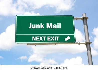 Green overhead road sign with a Junk Mail Next Exit concept against a partly cloudy sky background.