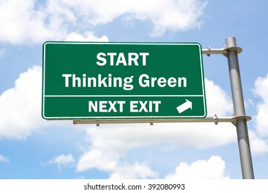 Green overhead road sign with a Start Thinking Green Next Exit concept against a partly cloudy sky background.