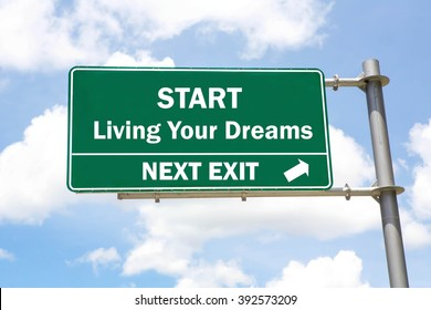 Green overhead road sign with a Start Living Your Dreams Next Exit concept against a partly cloudy sky background.