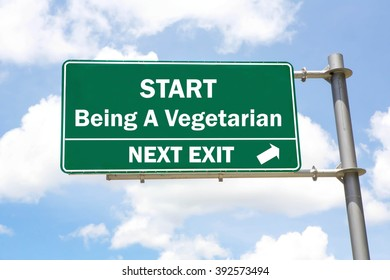 Green overhead road sign with a Start Being A Vegetarian Next Exit concept against a partly cloudy sky background.