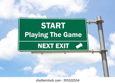 Green overhead road sign with a Start Playing The Game Next Exit concept against a partly cloudy sky background.