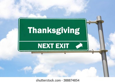 Green overhead road sign with a Thanksgiving Next Exit concept against a partly cloudy sky background.