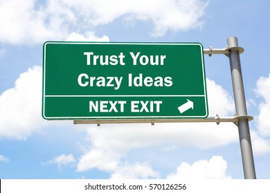 Green overhead road sign with a Trust Your Crazy Ideas Next Exit concept against a partly cloudy sky background.