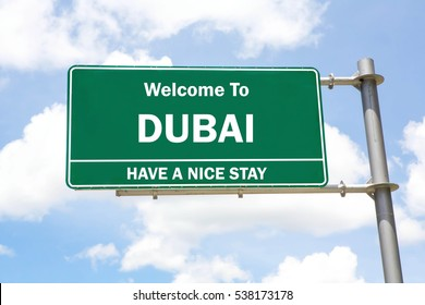 Green overhead road sign with a Welcome to Dubai, Have a Nice Stay concept against a partly cloudy sky background.
