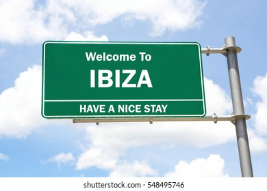 Green overhead road sign with a Welcome to Ibiza, Have a Nice Stay concept against a partly cloudy sky background.