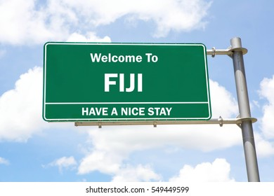 Green overhead road sign with a Welcome to Fiji, Have a Nice Stay concept against a partly cloudy sky background.