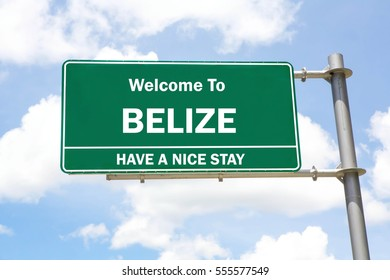 Green overhead road sign with a Welcome to Belize, Have a Nice Stay concept against a partly cloudy sky background.