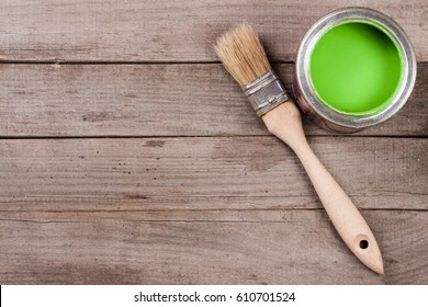 green paint in the bank to repair and brush on the old wooden background with copy space for your text. Top view
