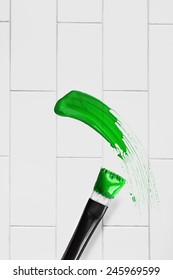 Green paint brush stroke over blank brick wall as a background