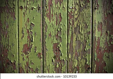 Green paint peeling from a wooden panel door showing the wood grain and old red painted surface