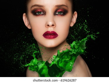 Green paint splash over beauty makeup fashion model girl with purple smokey eyes abstract on black background
