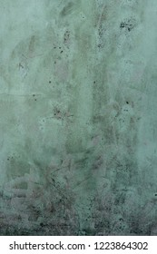 Green painted plastered wall with cracks and mouldy dirt